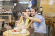 Beautiful couple taking selfie photo in cafe