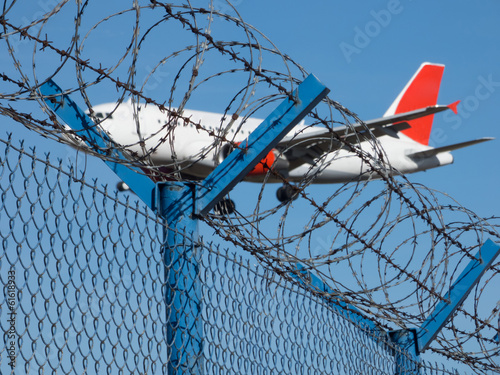 Landing airplane behind barbed wire