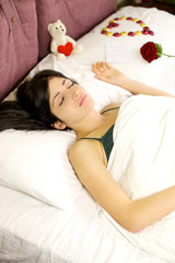 Woman sleeping with love gifts from lover