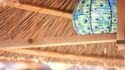 Beach wood umbrella with turquoise lamp at daytime