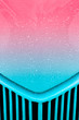 raindrops on a pink to turquoise vehicle grill