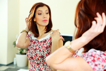 Beautiful woman looking on her reflection in the mirror at home