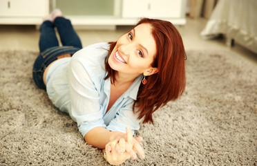 Smiling woman lying on the carpet at home