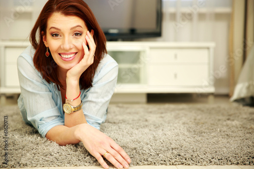 Smiling woman lying on the floor at home