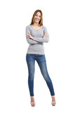 Full body of a casual happy woman standing wearing jeans