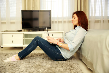 Side view portrait of a beautiful woman using laptop at home