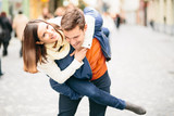 Couple having fun young man giving piggyback ride to girlfriend