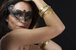Beautiful young woman in mysterious black Venetian mask. Fashion