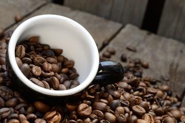 Schmackhafte Kaffeebohnen auf Holzuntergrund mit Tasse