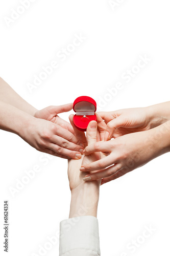 Isolated closeup shot of two jealous women taking ring from man