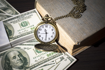 Still life of pocket watch on bills and old book