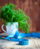 Cup with dill  and measure tape, place for your text on right, d