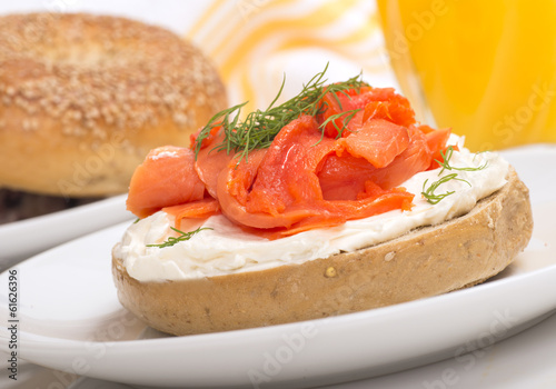 Freshly baked bagel with cream cheese, lox and orange juice