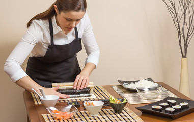 Portrait of woman chef rolling up a japanese sushi