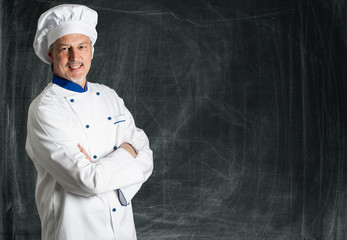 Chef posing against a blackboard