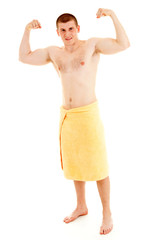young man in towel presents his muscles, white background