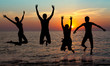 silhouette of jumping people on sunset background