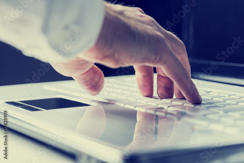 Man typing on a laptop keyboard