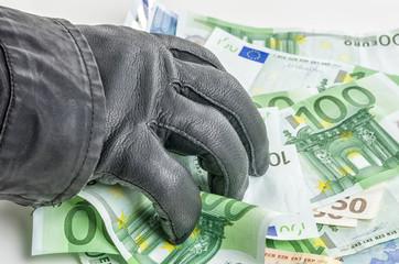 Dieb mit Lederhandschuh greift nach Geldscheinen