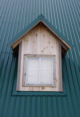 dormer with windows on the dark green roof