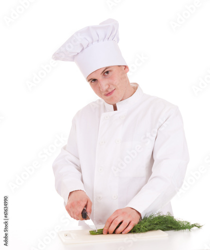 young male cook cutting dill, white background