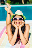 Relaxed woman sunbathing at swimming pool