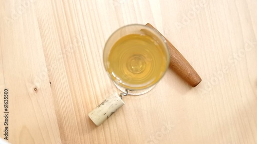 Corkscrew, cork and glass of white wine