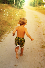 Boy running along road in park, outdoor