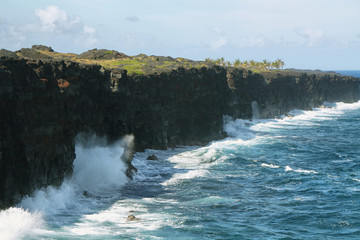 Waves crash along the black lava rock cliffs
