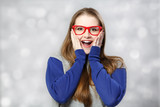 Surprised girl at red glasses at light background