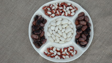 handful flowing in plate white beans next to colored beans