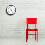 Red chair against white brick wall with clock