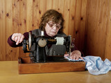 The old woman sews on the sewing machine