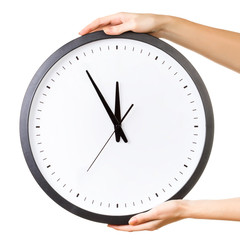 Woman holding a big clock isolated on a white background