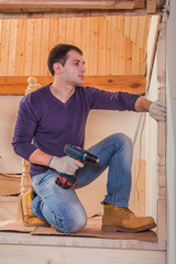 worker sitting and holding cordless drill