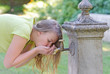 Woman drinking from public water fountain.