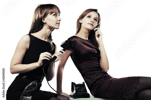 Two young women with a retro and cell phones