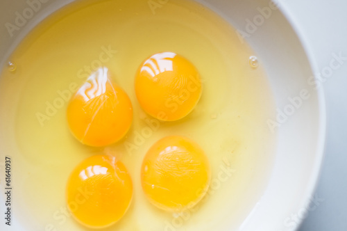 Four yellow egg yolks in a white bowl.