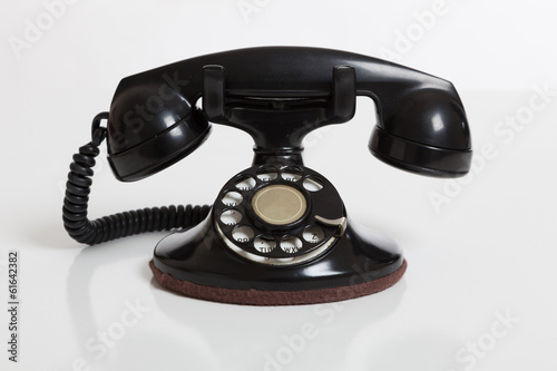 Black, vintage rotary phone on  white