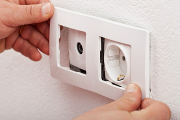 Male hands changing an electical wall outlet