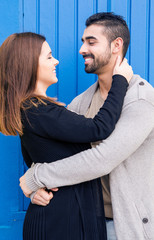 Couple hugging over blue background