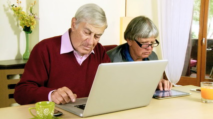 Senior couple writing email with tablet and pc