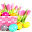 Easter basket with colorful eggs and flower background
