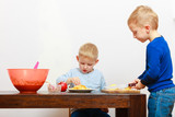 Blond boys children kids with kitchen knife cutting fruit apple