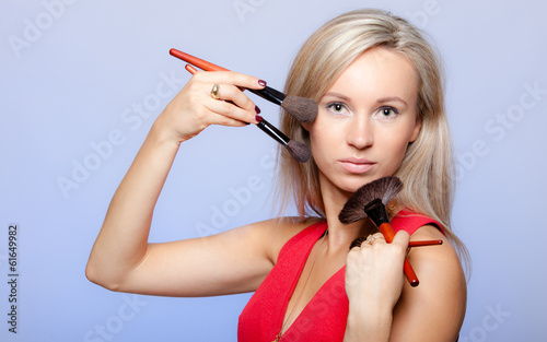 Blond girl stylist visagiste holding professional makeup brushes