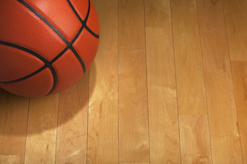 Basketball with spot lighting on wood gym floor