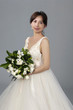 beautiful bride with a bouquet of flowers on gray background