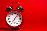 A red vintage alarm clock on a red background with copy space
