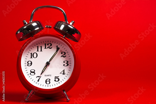 canvas print picture A red vintage alarm clock on a red background with copy space