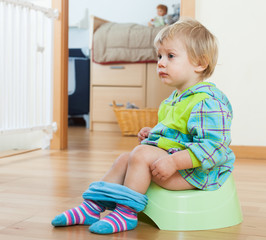Baby  sitting on green potty